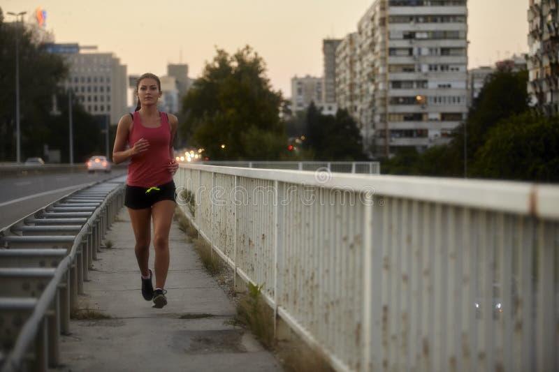 Une jeune femme, regardant à la caméra 20-29 ans, fonctionnement, seul pulsant sur un pont images libres de droits