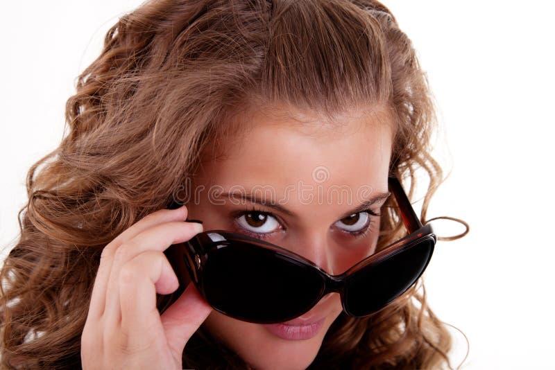 Une jeune femme regardant au-dessus de ses lunettes de soleil photographie stock libre de droits
