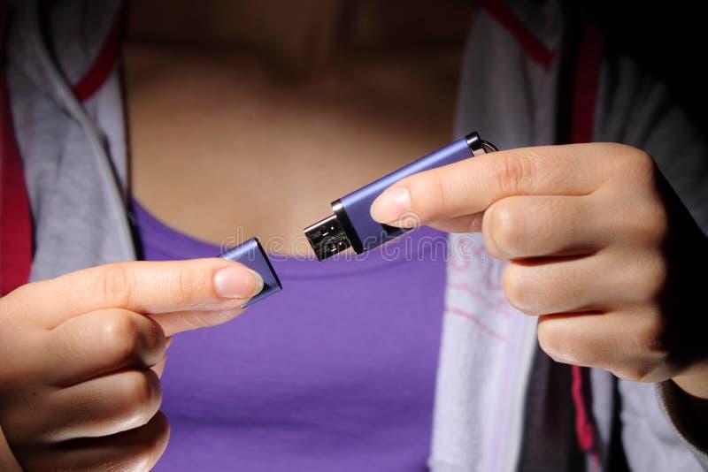 Une jeune femme retenant un bâton de mémoire Flash d'USB photos libres de droits