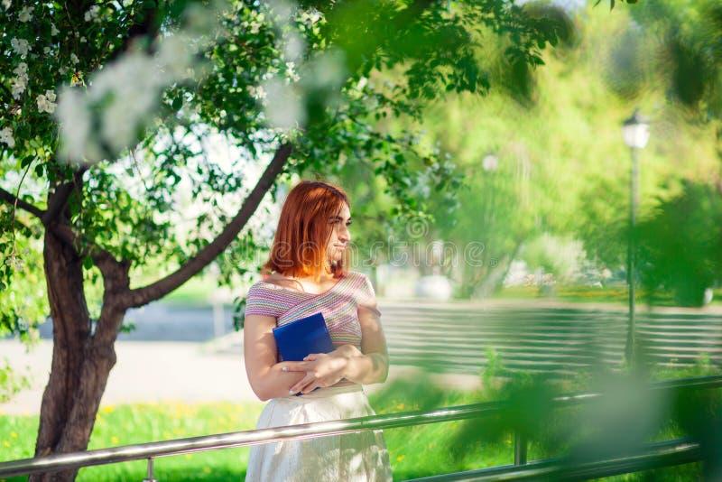 Une jeune femme rousse en parc photos stock