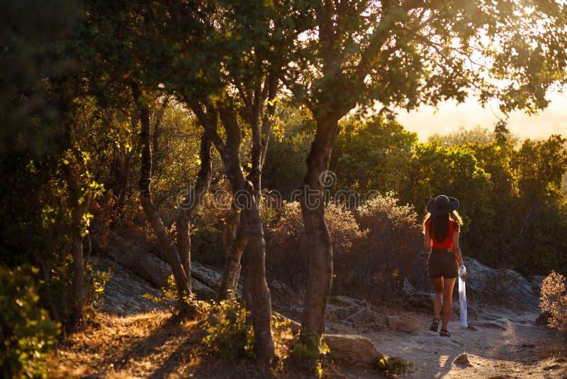 Une jeune femme s'asseyant de retour en nature stupéfiante d'île de Corse, France Fond de coucher du soleil Vue horizontale image libre de droits