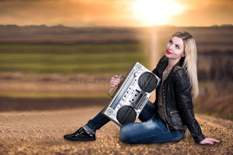 Une jeune femme s'assied sur la route et écouter un magnétophone de cru images libres de droits