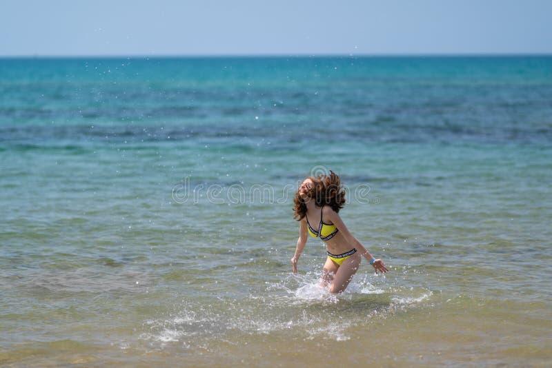 Une jeune femme sans souci se fraichissant dans la mer photo stock