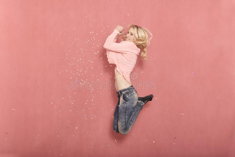 Une jeune femme, sautant dans le plein vol, souriant et heureux parce que confettis tombant vers le bas image stock