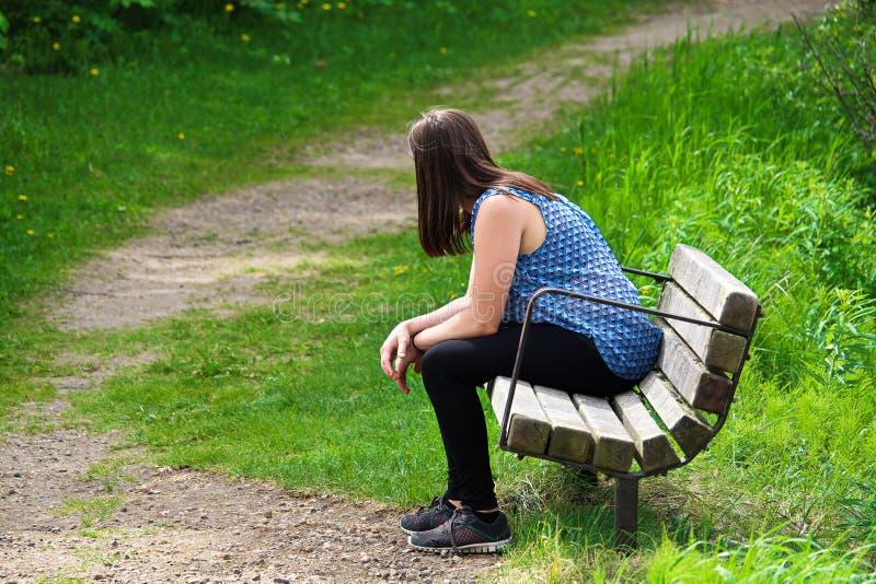 Une jeune femme se repose sur un banc en tant que vents d'une traînée autour de elle photos stock