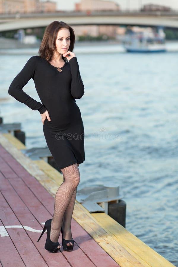 Une jeune femme se tenant sur le remblai photos stock