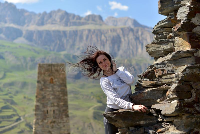 Une jeune femme se tient souriante près d'un mur ruiné contre une tour photographie stock libre de droits