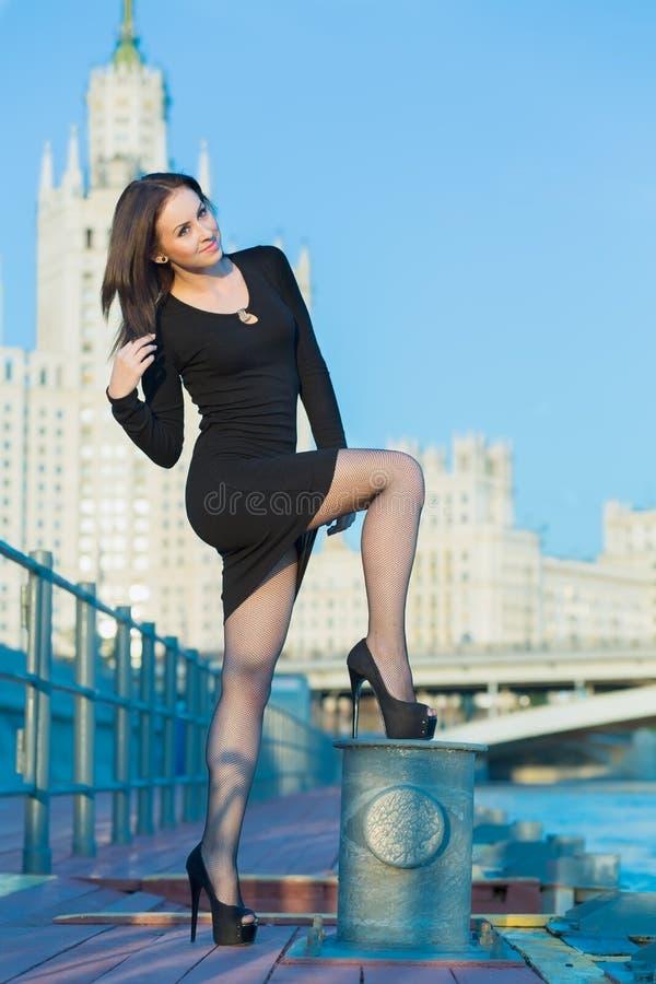 Une jeune femme se tient sur le bord de mer photo stock