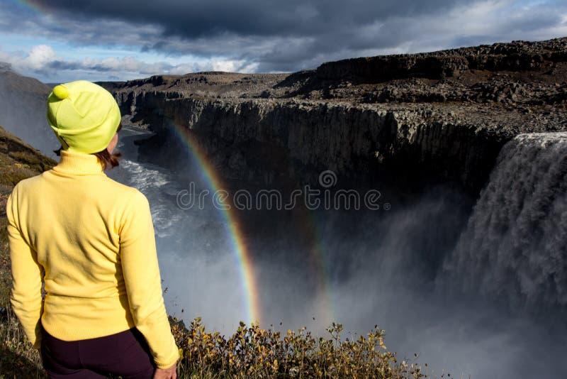 Une jeune femme se tient sur le rivage de l'eau en baisse de la cascade la plus puissante en Europe - Dettifoss Jour d'été coloré images stock