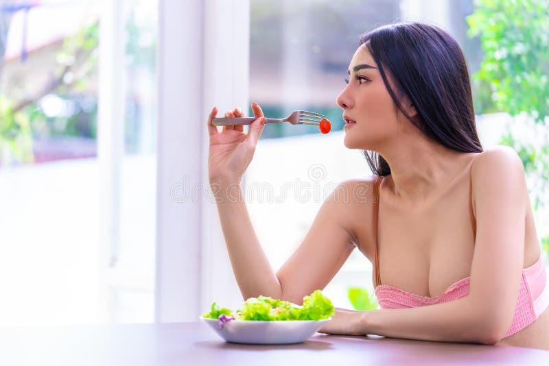 Une jeune femme sexy saine mange de la salade verte pour manger sain image stock