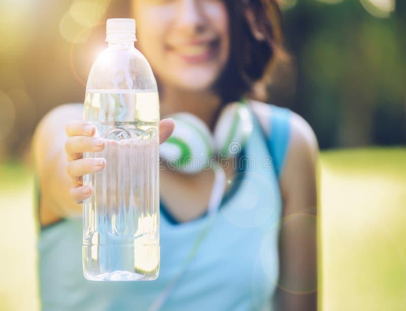 Une jeune femme tenant une bouteille de l'eau m'invitant à boire le wat photographie stock libre de droits