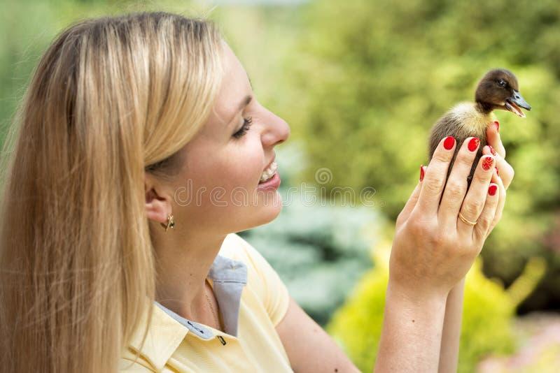 Une jeune femme, tenant un petit caneton images libres de droits