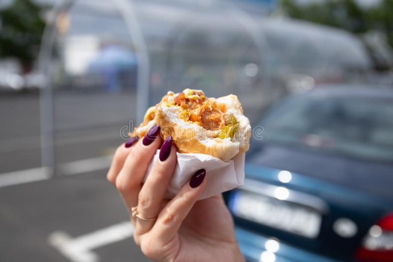 Une jeune femme tient un hot-dog mordu photos libres de droits