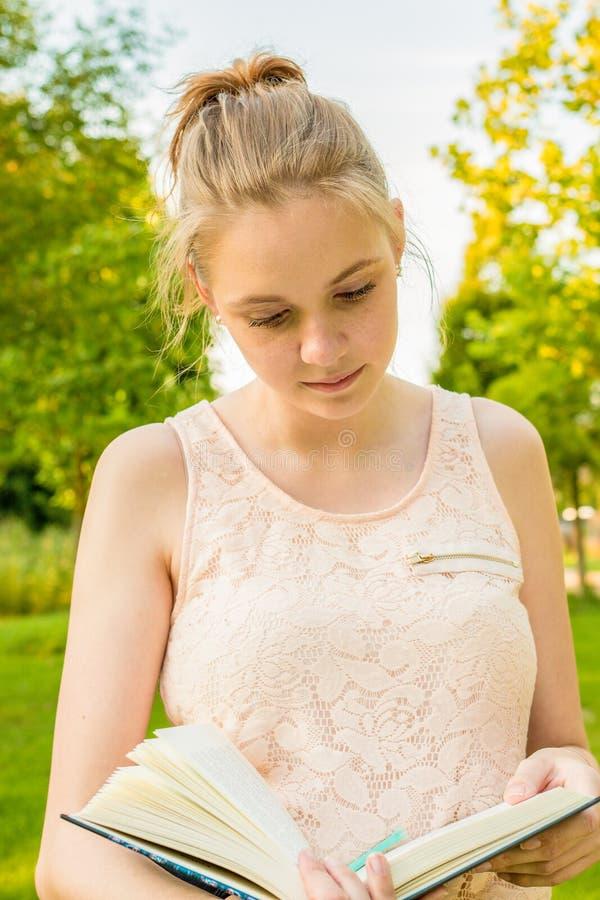 Une jeune femme tient un livre dans sa main en parc et lit en lui image stock
