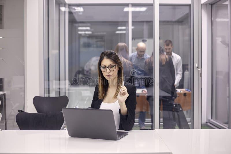 Une jeune femme travaillant sur l'ordinateur portable dans le bureau, groupe de travailleurs jouant au football de table dans l'a photos stock