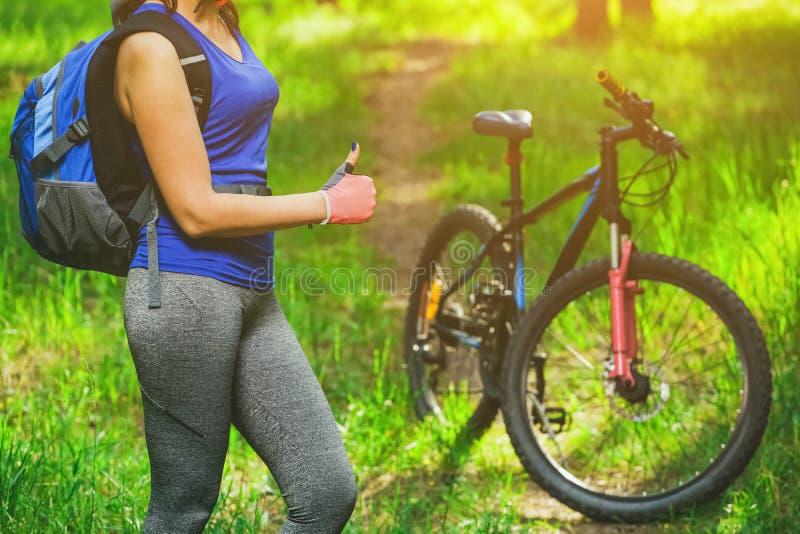 Une jeune femme - un athlète monte sur un vélo de montagne dans une forêt de pin photographie stock