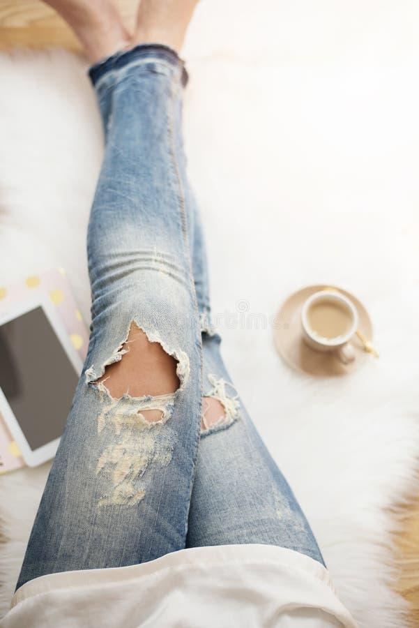 Une jeune femme utilisant les jeans affligés se reposant sur le plancher en bois sur un tapis blanc de fourrure à la maison Autou image stock
