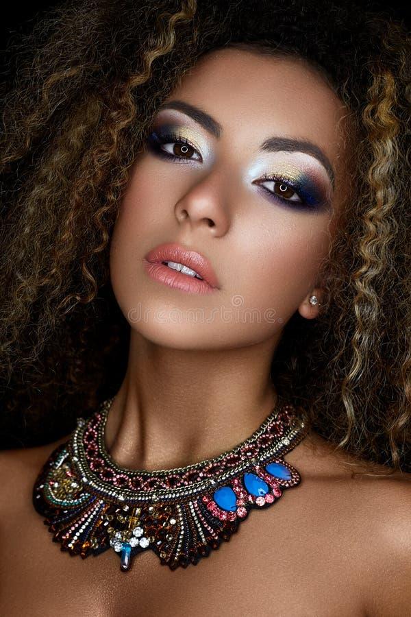 Une jeune fille afro-américaine avec le maquillage créatif et les petites boucles Un beau modèle avec la peau parfaite et un pend photos libres de droits
