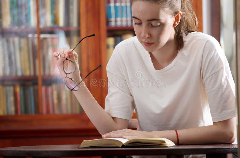 Une jeune fille apprend à la bibliothèque photo stock