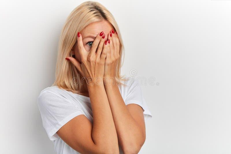 Une jeune fille aux cheveux clairs se couvrant le visage de mains, les yeux pleins de terreur images libres de droits