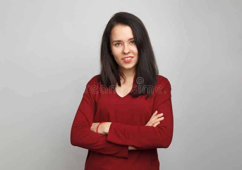 Une jeune fille aux cheveux foncés se tient droite les bras croisés, portant un chandail rouge au cou-v sur fond gris image stock