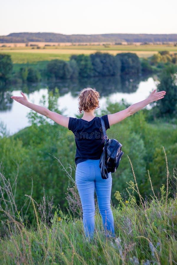 Une jeune fille avec augmenté ses mains appréciant l'unité avec le natu photo libre de droits