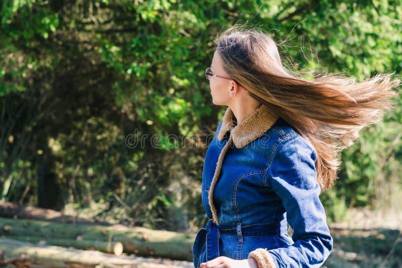 Une jeune fille avec de longs cheveux blonds et une veste de denim examine la distance dans une forêt conifére verte image libre de droits