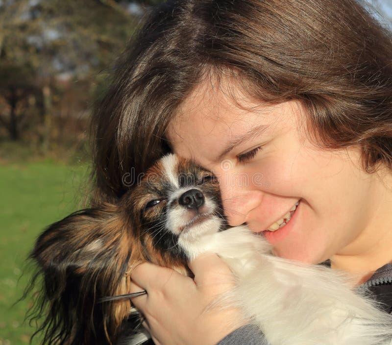 Une jeune fille avec de longs cheveux bruns tient un petit chien velu - son animal familier photographie stock