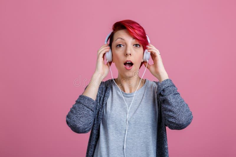 Une jeune fille avec avec des écouteurs, avec un regard étonné, ouvrant sa bouche photographie stock