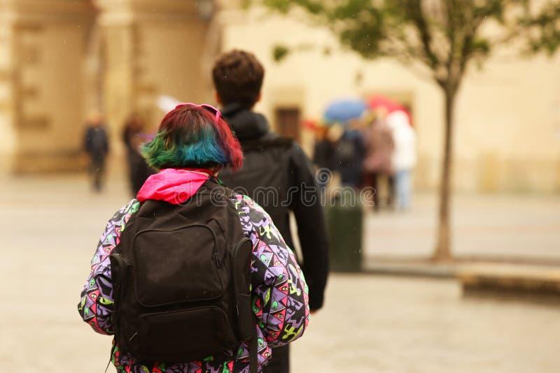 Une jeune fille avec des cheveux multicolores et une coupe de cheveux à la mode marche autour de la ville avec un sac à dos Prote image stock
