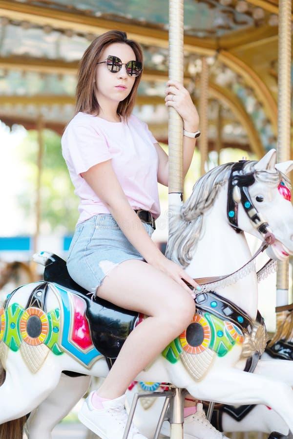 Une jeune fille avec des verres montant sur des chevaux d'un carrousel photo stock