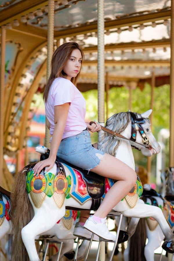 Une jeune fille avec des verres montant sur des chevaux d'un carrousel images stock