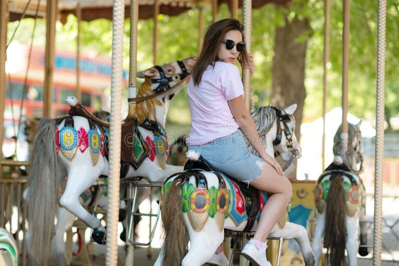 Une jeune fille avec des verres montant sur des chevaux d'un carrousel image libre de droits