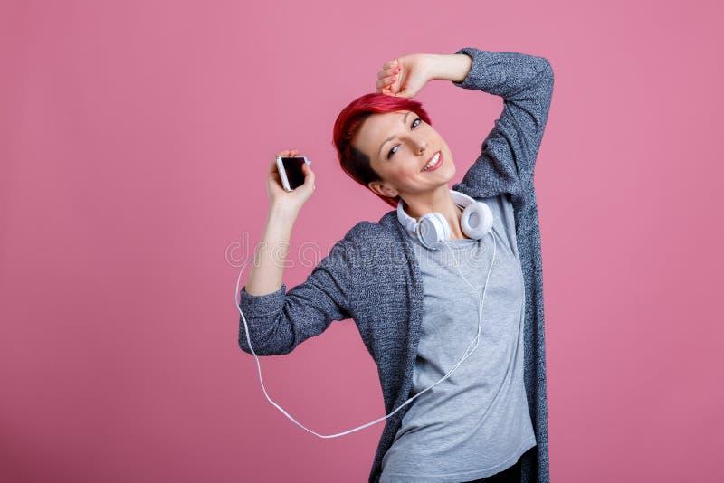Une jeune fille avec les cheveux rouges est danse, écoutant la musique sur des écouteurs image stock