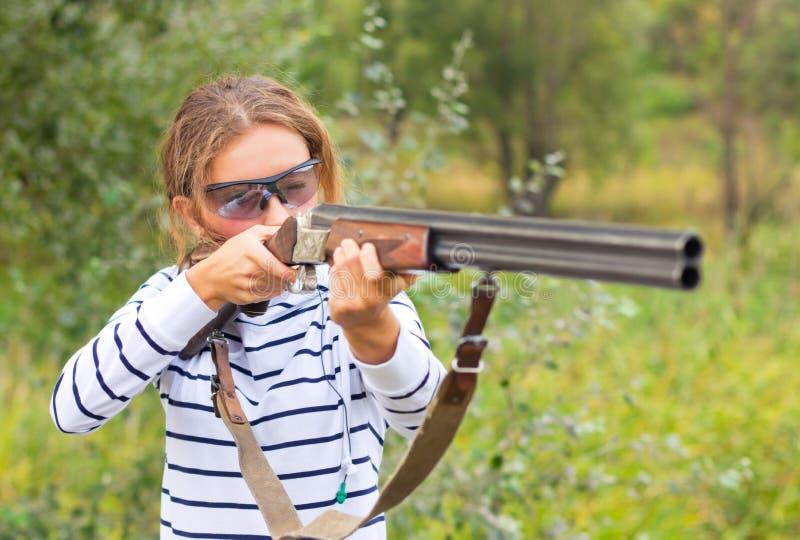 Une jeune fille avec un canon pour le tir de trappe photos stock