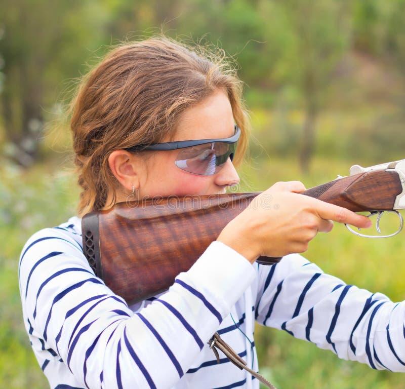 Une jeune fille avec un canon pour le tir de trappe images stock