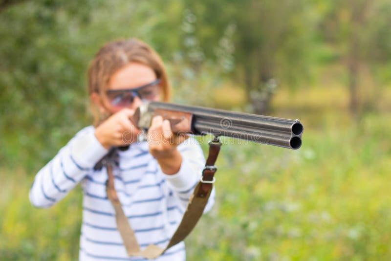 Une jeune fille avec un canon pour le tir de trappe photos libres de droits