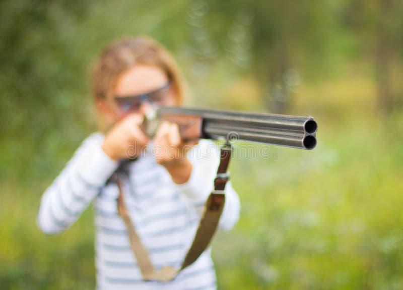 Une jeune fille avec un canon pour le tir de trappe photo libre de droits