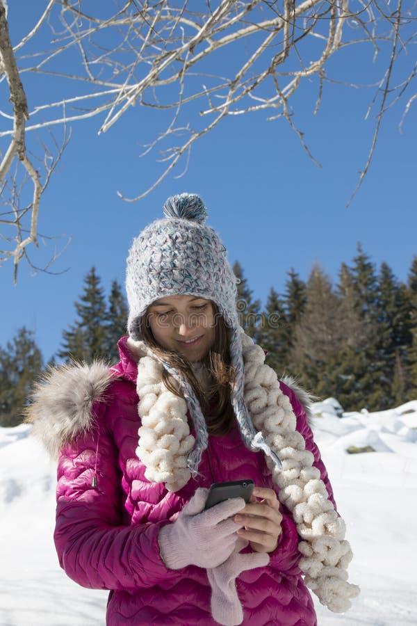 Une jeune fille avec un smartphone dans les montagnes en hiver image stock
