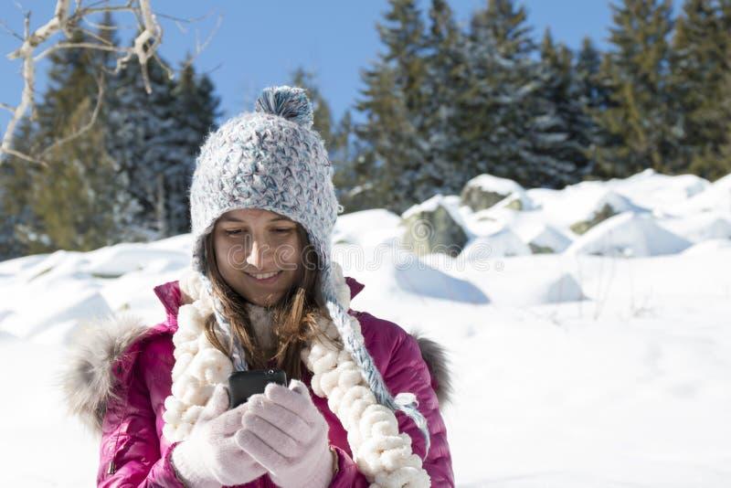 Une jeune fille avec un smartphone dans les montagnes en hiver images stock