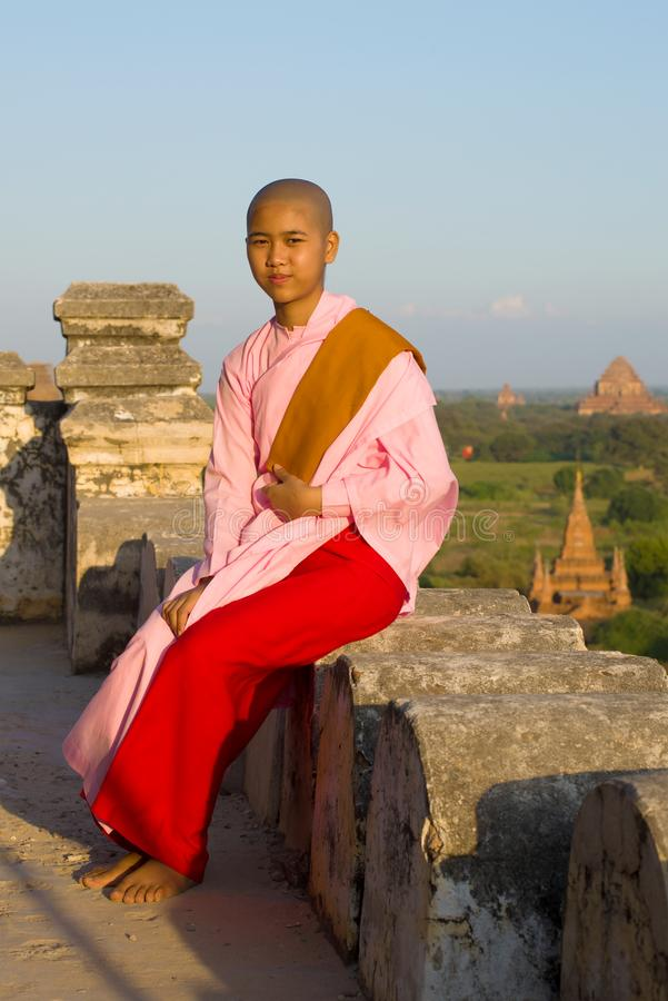 Une jeune fille birmanne de nonne s'assied sur le parapet d'un temple bouddhiste antique images libres de droits