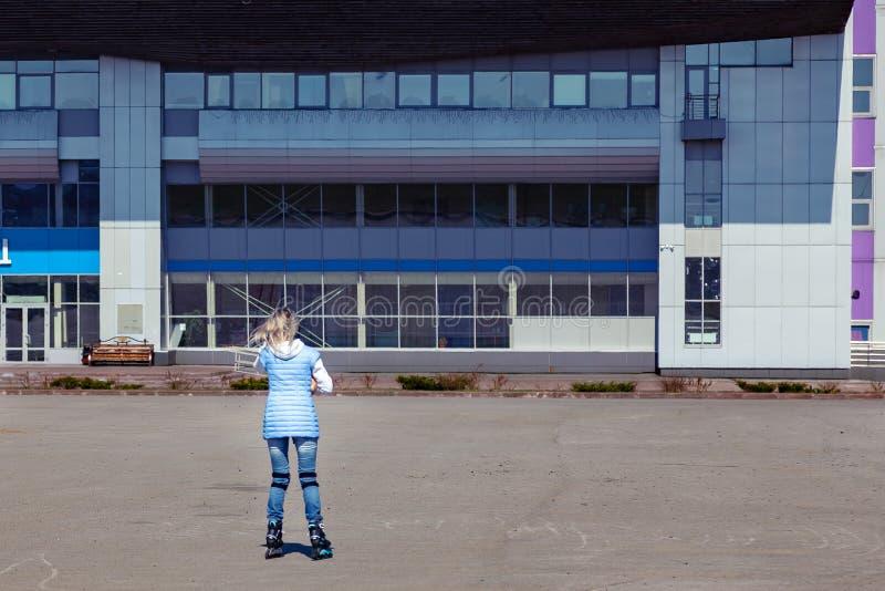 Une jeune fille blonde dans une veste bleue fait du patin ? roulettes autour de la place pour des promenades et du repos sur un e image libre de droits