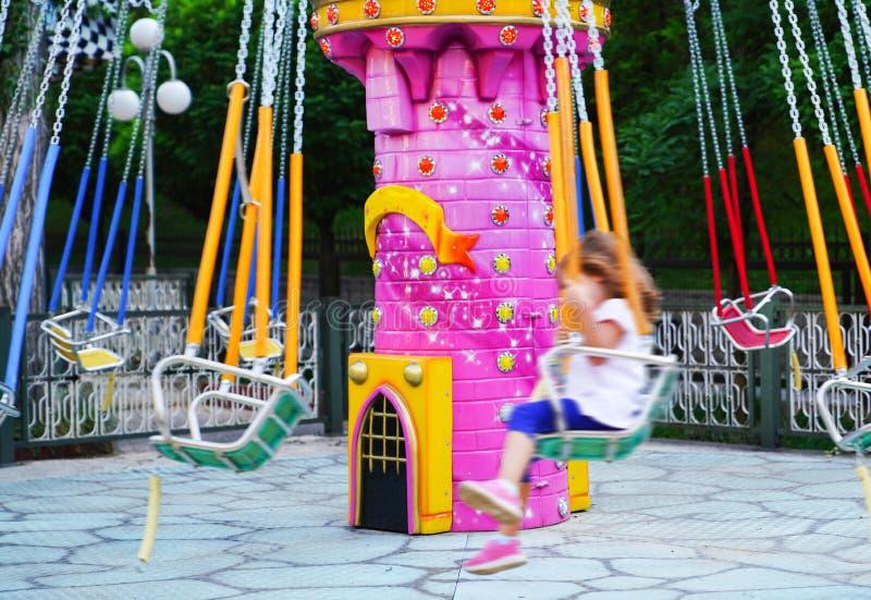 Une jeune fille brouillée montant une oscillation à chaînes de carrousel images libres de droits