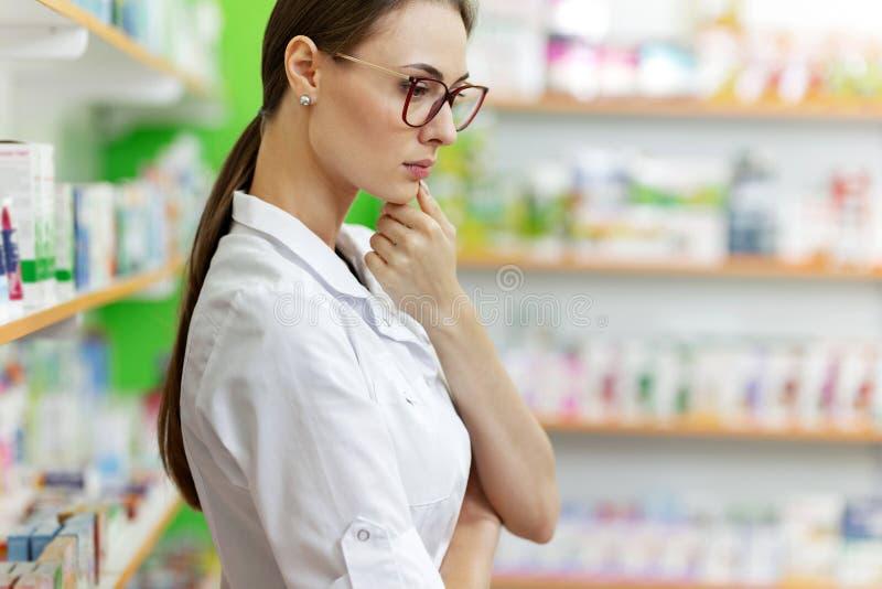 Une jeune fille châtain mince avec des verres, habillés dans une combinaison médicale, se tient avec le regard de couvée à côté d photo stock