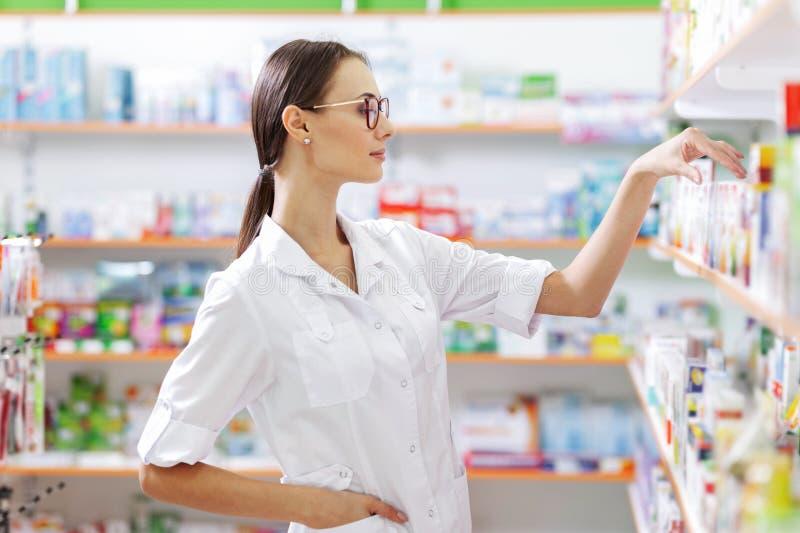 Une jeune fille châtain mince avec des verres, habillés dans un manteau de laboratoire, prend quelques médecines de l'étagère dan images libres de droits