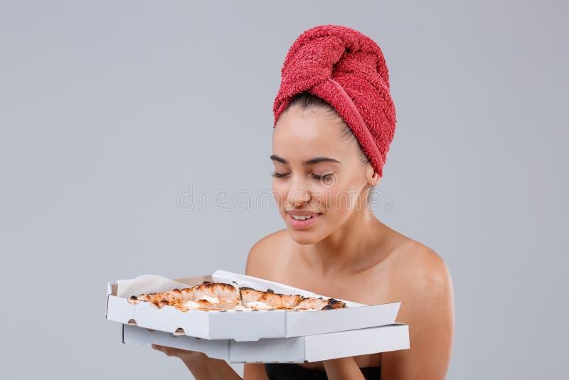Une jeune fille, conserve un paquet de pizzas appétissantes tout en appréciant l'odeur parfumée image stock