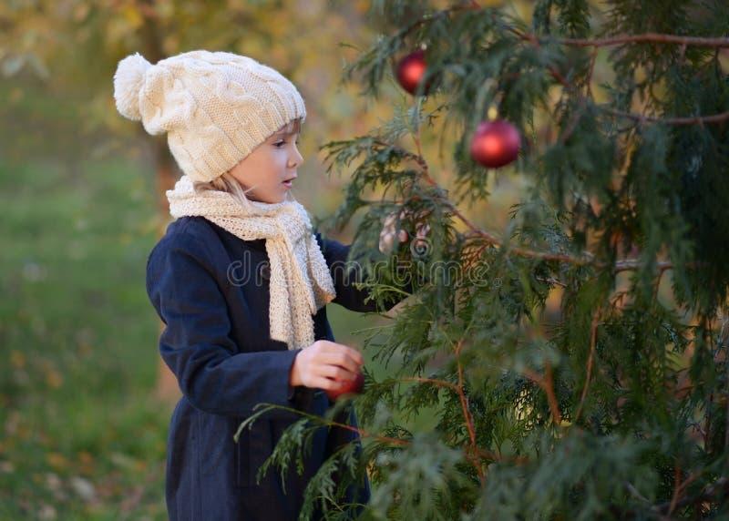 Une jeune fille décorant un sapin image stock