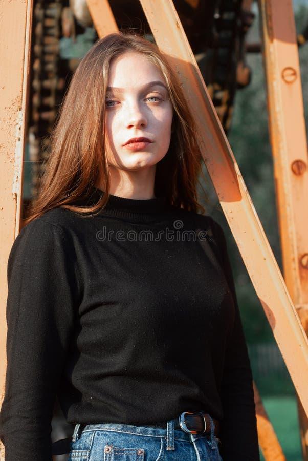 Une jeune fille dans des blues-jean posant sur un fond des constructions métalliques, images libres de droits