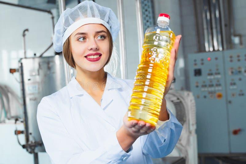 Une jeune fille dans des combinaisons blanches tient une bouteille d'huile de tournesol image stock