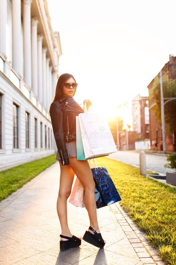 Une jeune fille dans des lunettes de soleil, apprécie des achats réussis, agains image stock